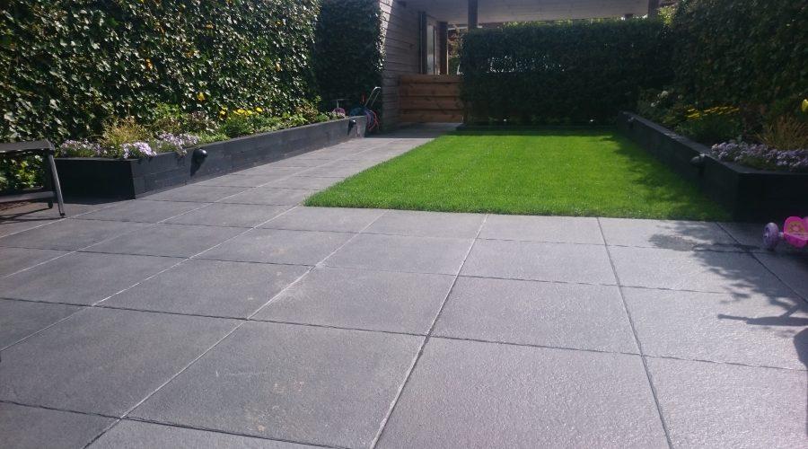 Praktische tuin met mooie grote donkergrijze tegels
